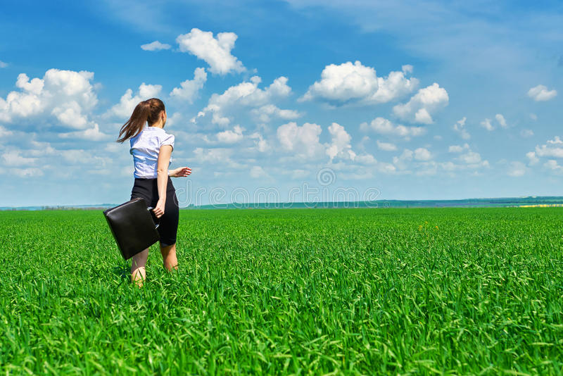 La passeggiata della donna di affari sul campo di erba verde all'aperto e si rilassa sotto il sole La bella ragazza si è vestita  fotografia stock