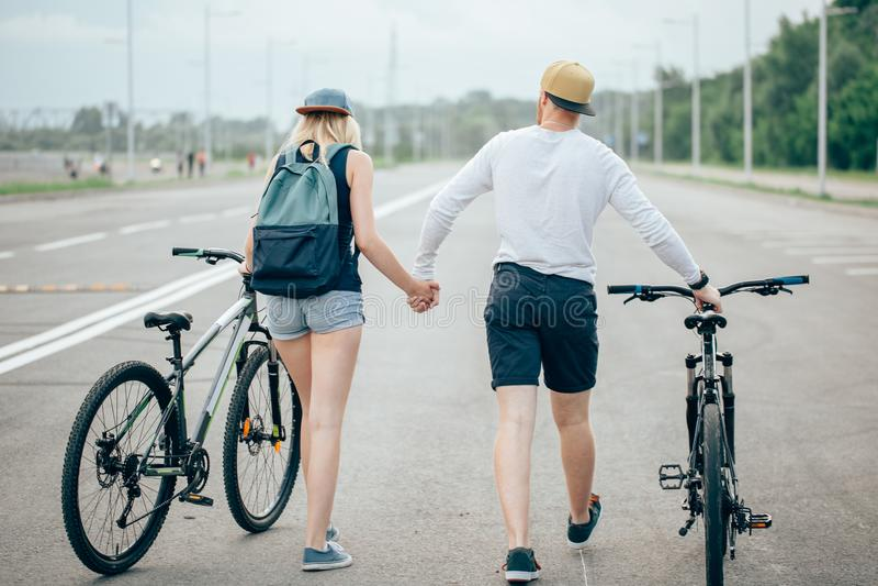 La passeggiata della donna e dell'uomo le loro bici si scola la strada fotografie stock