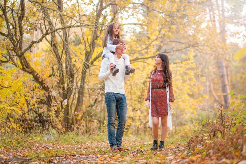 La passeggiata della mamma, del papà e della figlia attraverso la figlia della foresta di autunno si siede sulle spalle del padre immagini stock