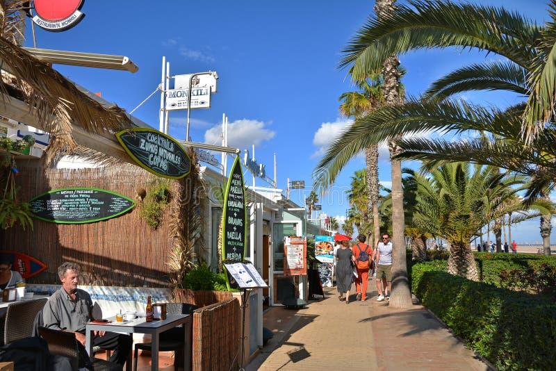 La passeggiata della parte anteriore di mare con gli hotel ed i ristoranti a Malvarrosa tirano fotografia stock
