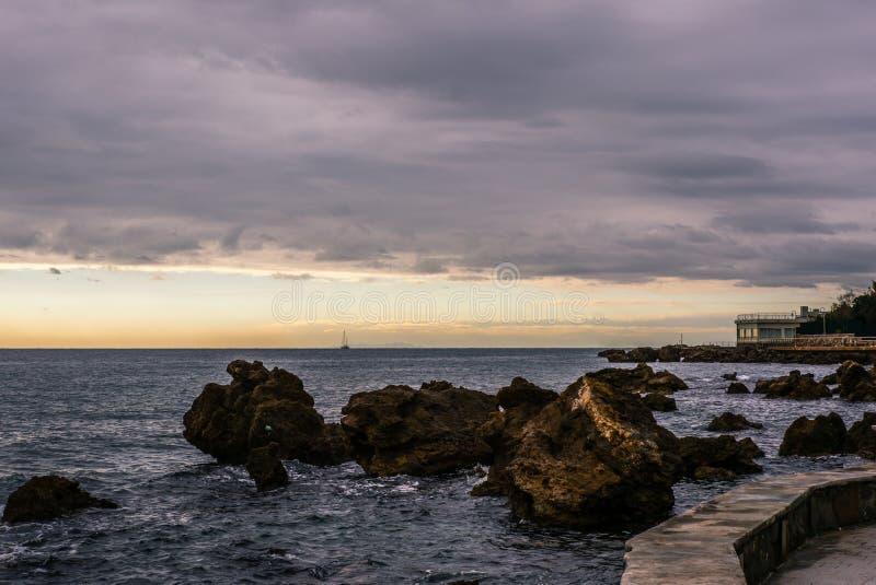 La passeggiata di Castiglioncello in Toscana nell'inverno al tramonto con un'isola e una barca a vela sull'orizzonte - 3 fotografia stock