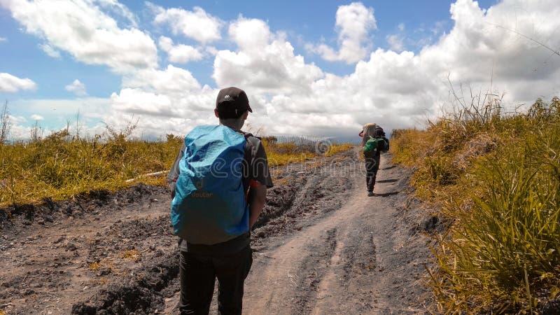 La passeggiata di viaggiatori con zaino e sacco a pelo nella via fotografie stock libere da diritti
