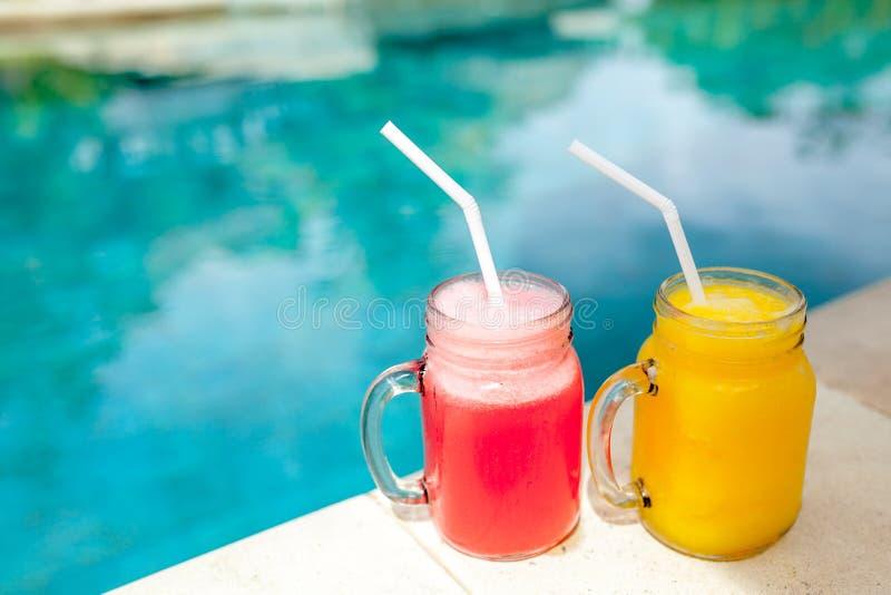 La pastèque et la mangue ont glacé des smoothies dans le pot sur le fond de piscine photos libres de droits