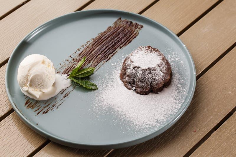 La pasta de azúcar fresca deliciosa con el chocolate caliente y helado y menta sirvió en la placa Receta de la torta de la lava F imagen de archivo libre de regalías