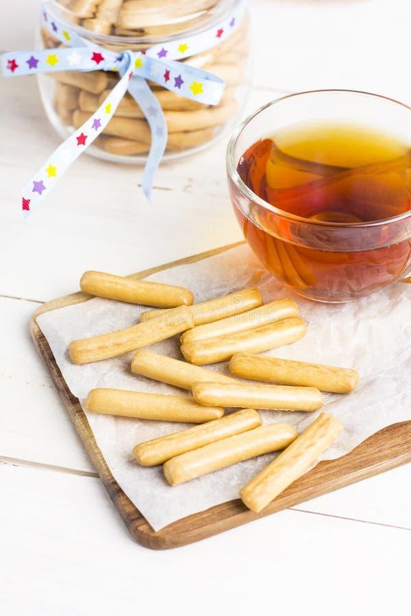 La pasta de hojaldre se pega en el papel de la panadería con la taza de té imagenes de archivo