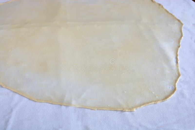 La pasta hecha en casa de Phyllo o del milhojas en un mantel casero, alista para el banitsa, el milhojas de manzana, el baklava,  foto de archivo