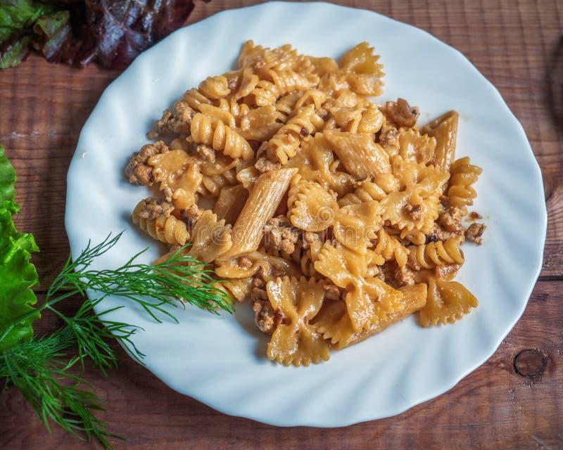 La pasta scura della farina della prima colazione nutriente calda con la Turchia ha tritato la carne su un piatto bianco immagini stock libere da diritti