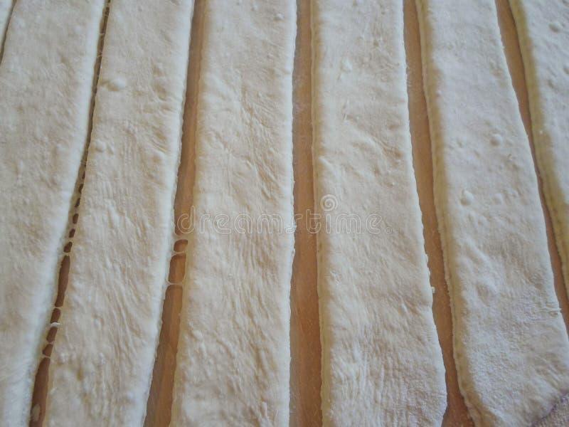 La pasta se corta en líneas verticales en un tablero de madera Fondo L?nea vertical imagen de archivo
