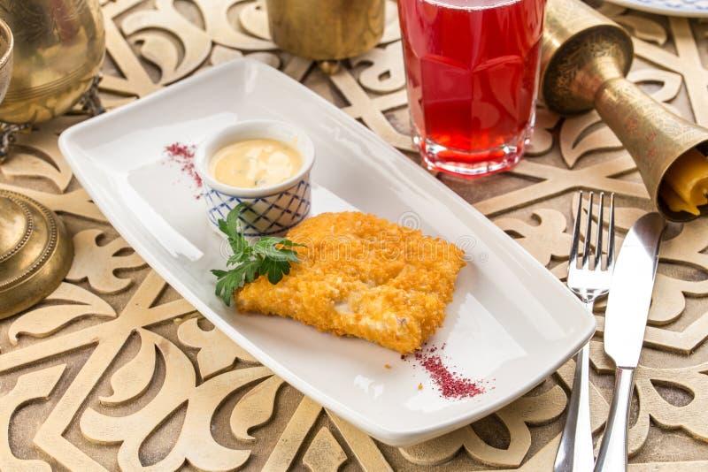 La pastella dorata deliziosa ha fritto nel grasso bollente i filetti di pesce serviti sul piatto bianco sulla tavola orientale fotografie stock