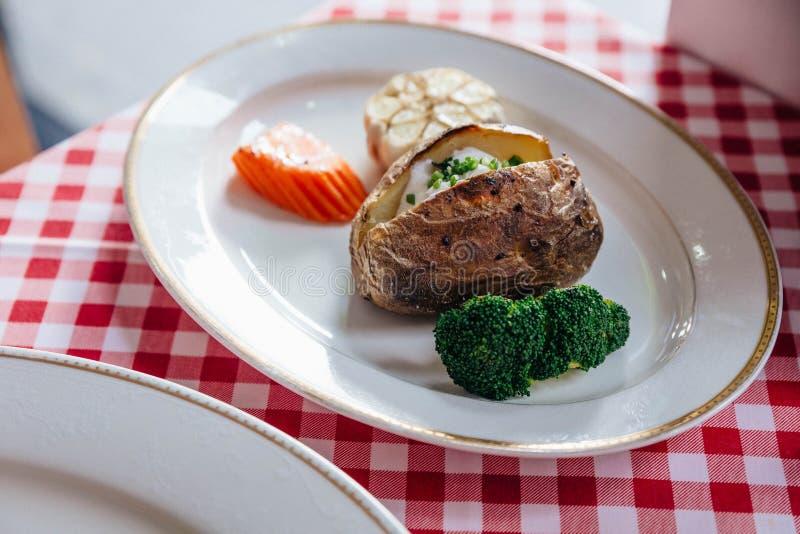 La patata cocida sirvió con la zanahoria, el maíz y el bróculi asados a la parrilla en la placa blanca en mantel rojo y blanco de fotos de archivo