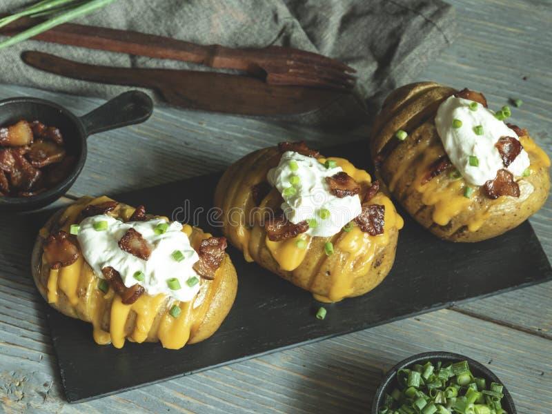 La patata cotta farcita con formaggio, bacon e panna acida ha caricato le patate del hasselback immagine stock