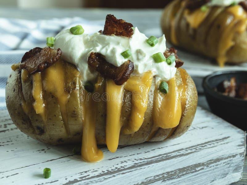 La patata cotta farcita con formaggio, bacon e panna acida ha caricato le patate del hasselback fotografia stock