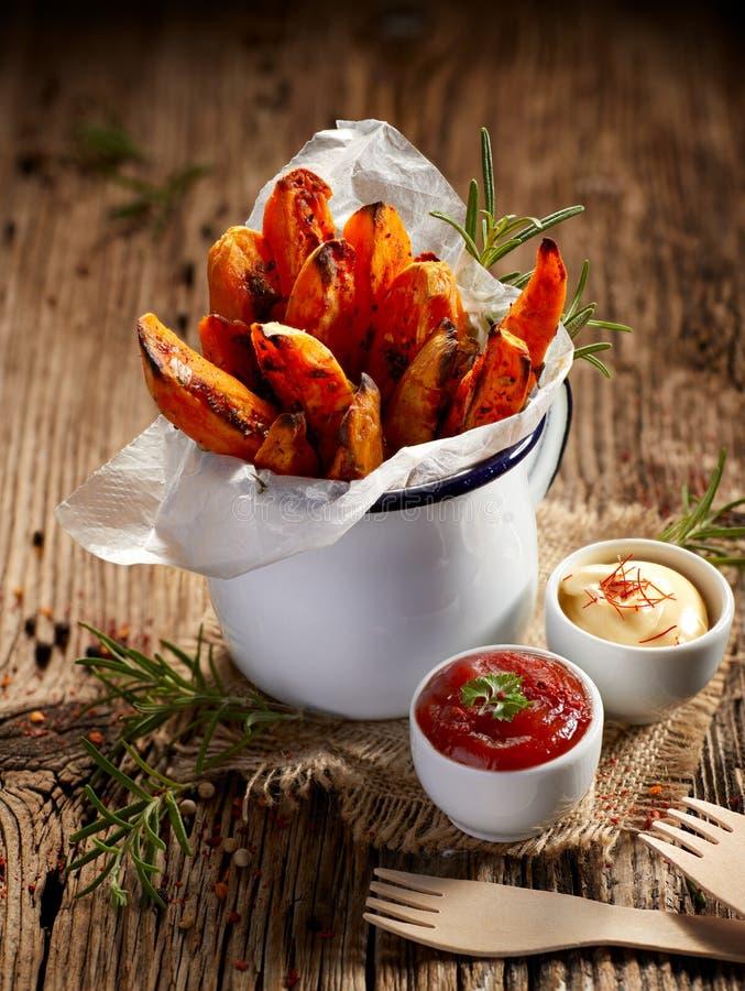 La patata dulce fríe las hierbas y la sal sazonadas del mar en taza del esmalte en una tabla de madera imagen de archivo