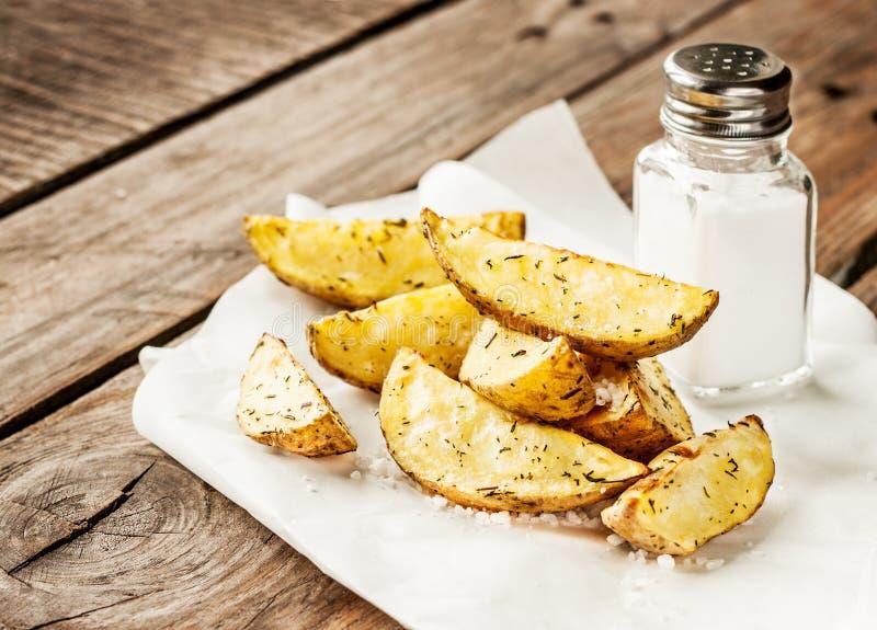 La patata incunea sulla tavola di legno rustica - escluda il menu fotografie stock
