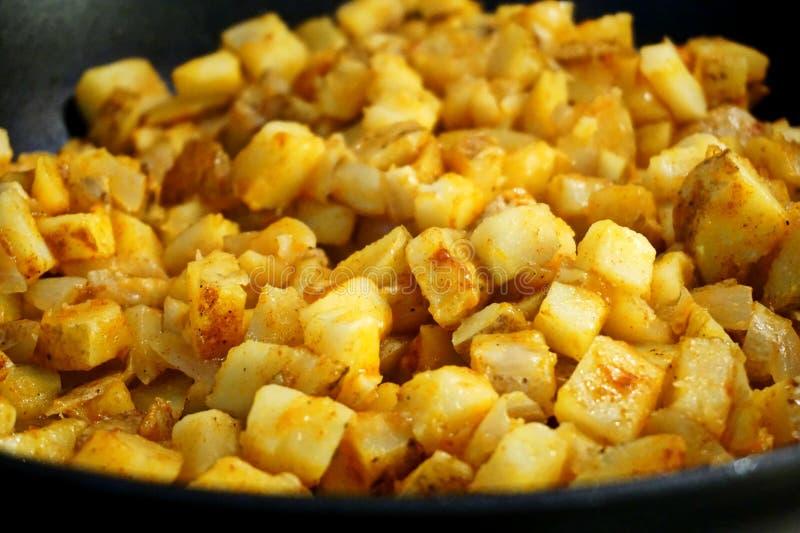 La patata sminuzza in una padella fotografie stock