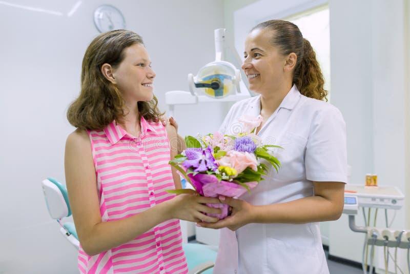 La patiente de fille donne un bouquet des fleurs à un docteur féminin dans le bureau dentaire Jour national du ` s de dentiste photographie stock libre de droits