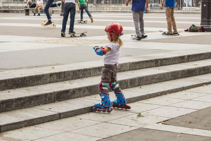 La patineuse de jeune fille dans le premier plan ajuste ses gants protecteurs W photos stock