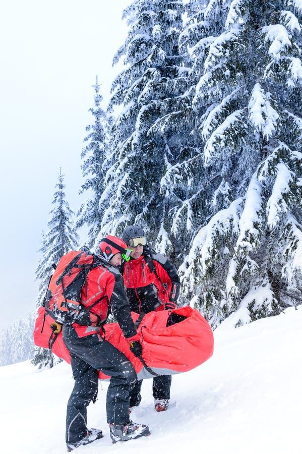 La patrulla del esquí lleva a la persona herida en ensanchador foto de archivo libre de regalías