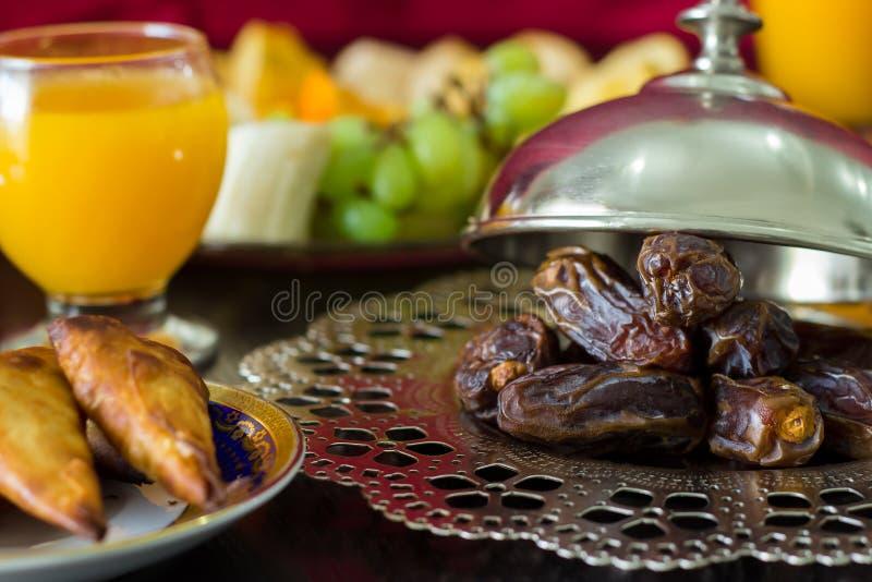 La paume de datte sèche porte des fruits, jus d'orange frais, casse-croûte de samosa et fruit brouillé images stock