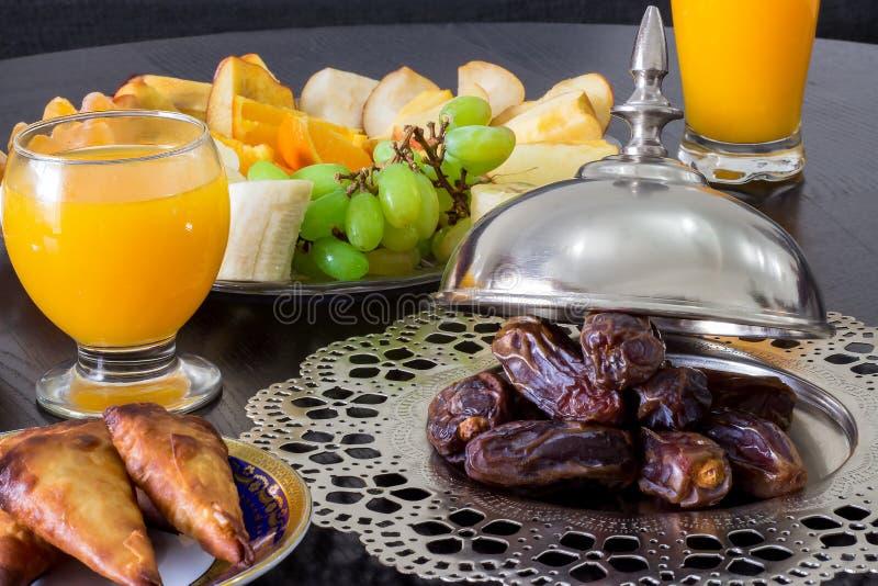 La paume de datte sèche porte des fruits, jus d'orange frais, casse-croûte de samosa et fruit brouillé photos stock