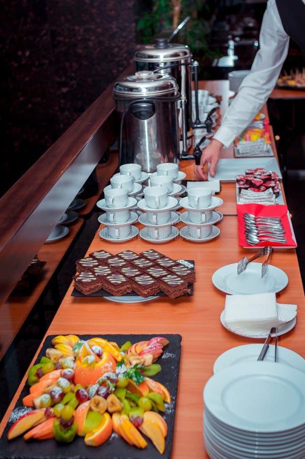 La pausa caffè è servito pezzi sul †della tavola «di dolce di cioccolato sul vassoio di pietra nero, sui frutti e sulle tè-tazz fotografia stock