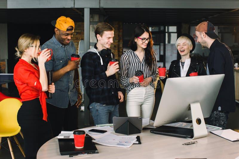 La pause pour d?tendent au travail Équipe heureuse de travail pendant le temps de coupure dans le bureau moderne léger, parlant,  photo libre de droits