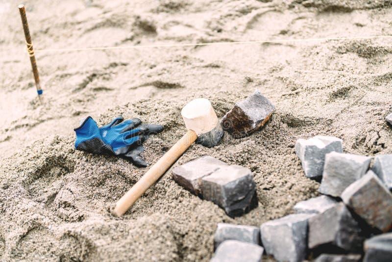 la pavimentazione industriale del ciottolo installa i dettagli Sabbia, guanti, martello di gomma e mattonelle del ciottolo sul ca fotografie stock