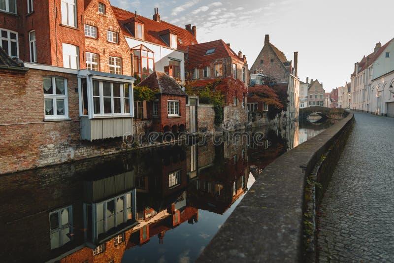 la pavimentazione sulla via stretta e le costruzioni hanno riflesso in acqua calma del canale a Bruges, Belgio fotografia stock