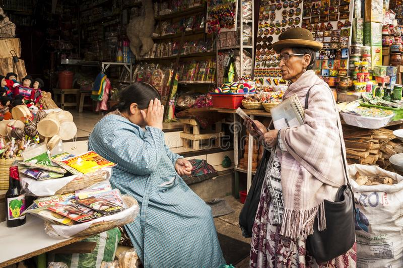 Unidentified street woman vendor selling offerings, souvenirs, mesas for rituals with dried llama fetuses stock image