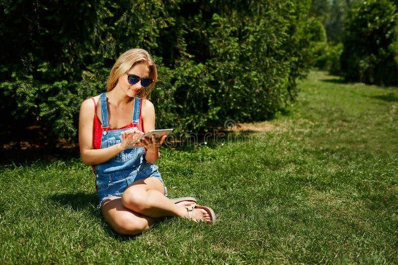 La PC blondy joven feliz de la tableta del uso del estudiante universitario de la mujer se sienta en GR imagenes de archivo