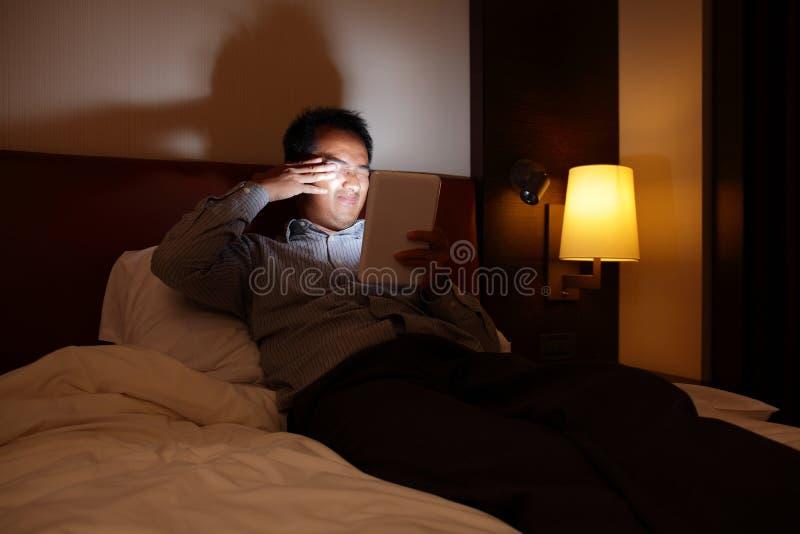 La PC de la tableta dañará sus ojos en la oscuridad fotografía de archivo