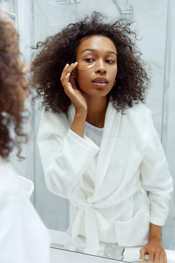 La peau des yeux Une femme applique un masque oculaire au visage dans la salle de bains images stock