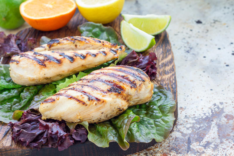La pechuga de pollo asada a la parrilla en adobo de la fruta cítrica en las hojas de la ensalada y el tablero de madera, horizont fotografía de archivo libre de regalías