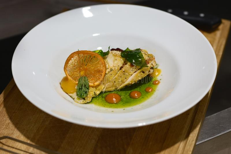 La pechuga de pollo sabrosa cortada con la mandarina y la espinaca sauce, adornado con una parte de la naranja y de verdes fotografía de archivo libre de regalías