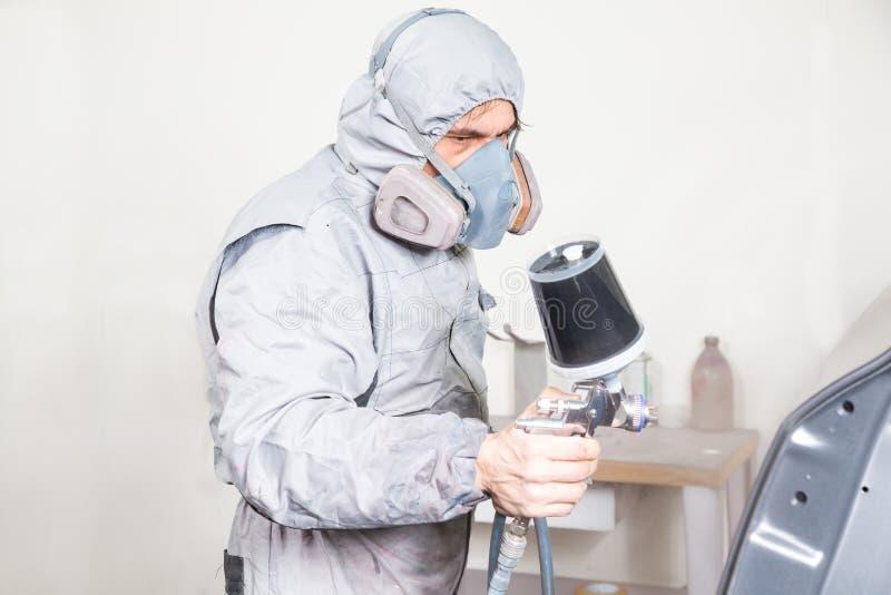 La peinture de pulvérisation de peintre de carrosserie sur la carrosserie partie photographie stock libre de droits