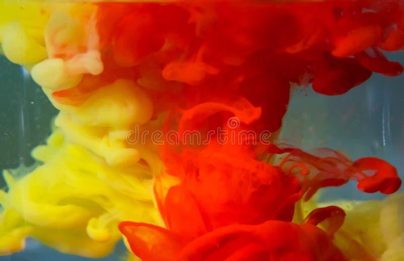 La peinture rouge et jaune se dissout lentement dans l'eau claire photographie stock libre de droits