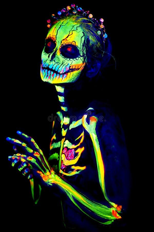 La peinture UV d'art de corps de helloween le squelette femelle photographie stock