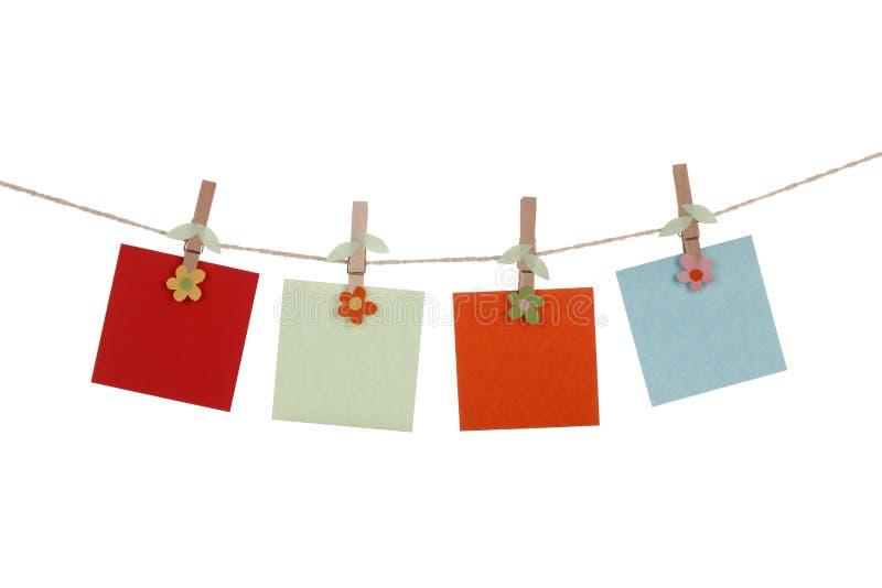 Tarjetas de papel en blanco que cuelgan en clothespins fotografía de archivo libre de regalías
