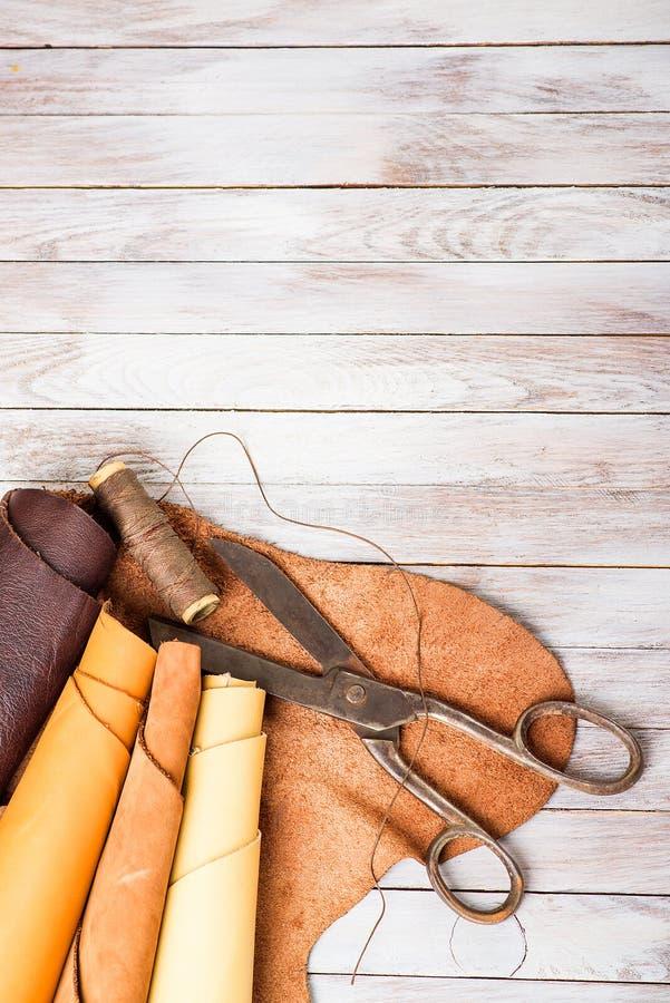 La pelle rotola con le forbici ed il filo su un fondo di legno fotografia stock libera da diritti