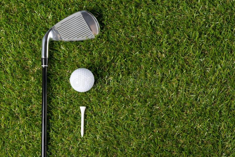 La pelota de golf con la camiseta y el putter de madera miente contra la perspectiva de hierba foto de archivo