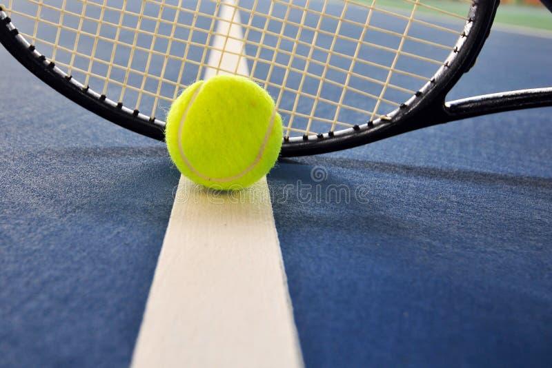 La pelota de tenis y la raqueta en una corte alinean foto de archivo libre de regalías