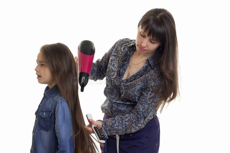 la Peluquero-mujer seca a la pequeña muchacha linda del pelo largo imagen de archivo libre de regalías