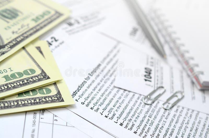 La penna, il taccuino e le banconote in dollari è bugie sulla forma 1040 di imposta immagini stock libere da diritti