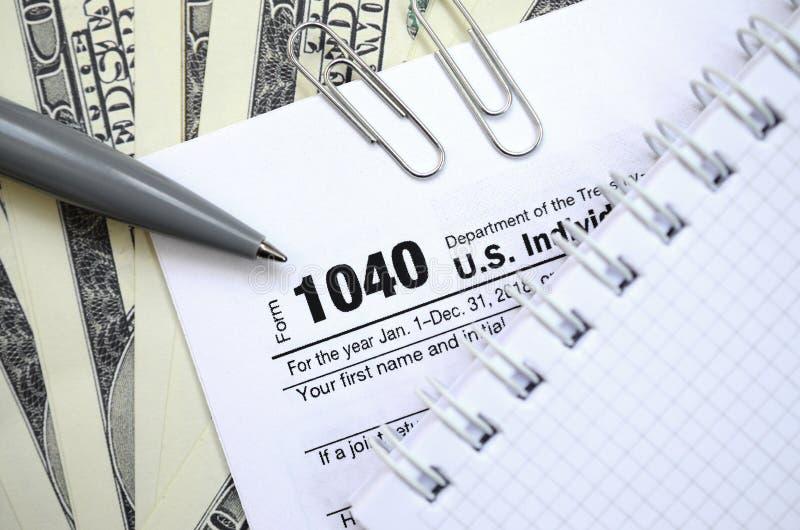 La penna, il taccuino e le banconote in dollari è bugie sulla forma 1040 di imposta immagine stock libera da diritti