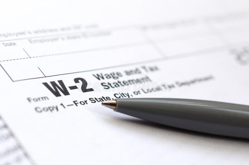 La penna si trova sulla dichiarazione dello stipendio e di imposta della forma W-2 di imposta Il Tim fotografia stock libera da diritti