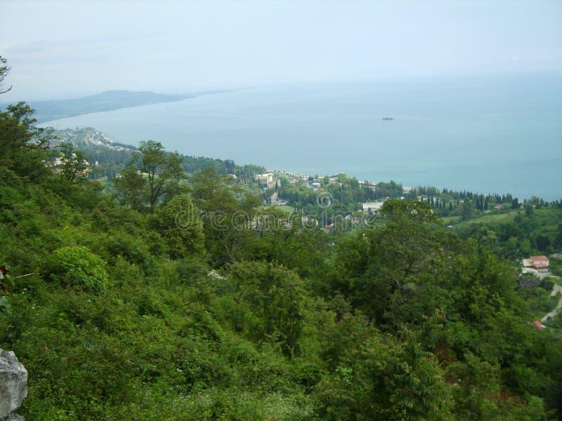 La pente de la montagne donnant sur la mer sans fin et le ciel bleu photographie stock libre de droits