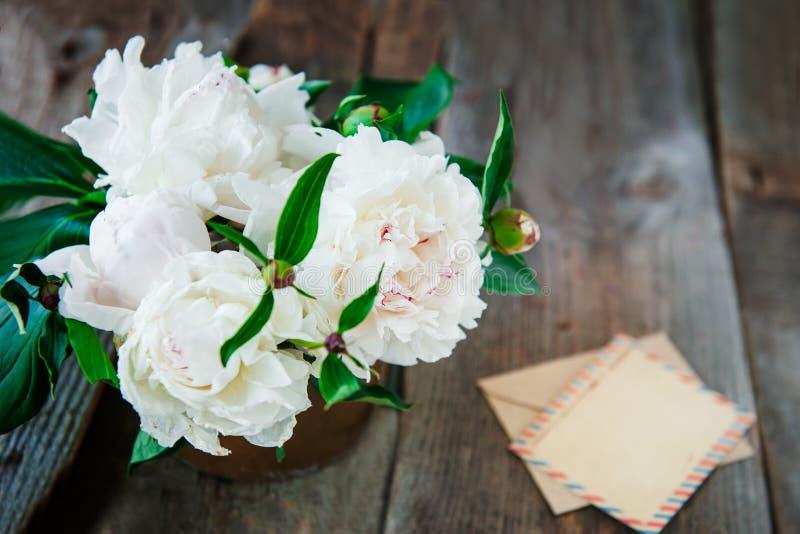 La peonía blanca de la visión superior florece el ramo, la tarjeta de felicitación en blanco y el sobre de papel del arte en el v fotos de archivo