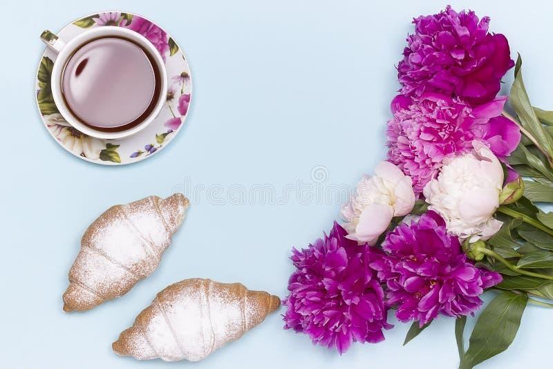 La peonía florece la taza de té del cruasán en fondo azul foto de archivo