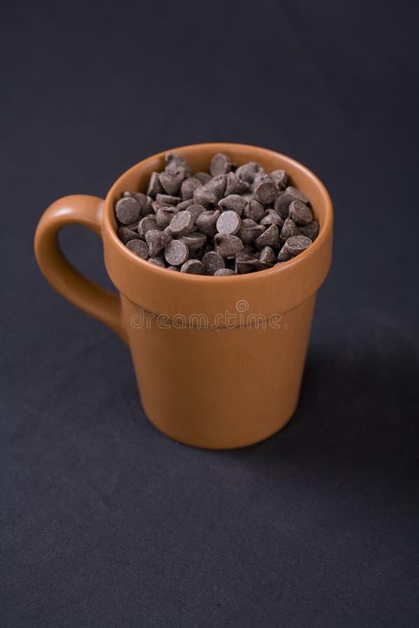 La pepita di cioccolato del Vegan dentro la tazza di terracotta fotografia stock