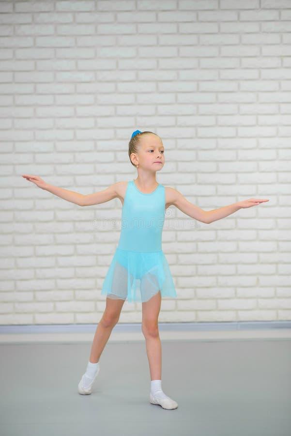 La pequeña bailarina en zapatos azules del vestido y del pointe está bailando en escuela del ballet Muchacha linda en clase de da imagenes de archivo